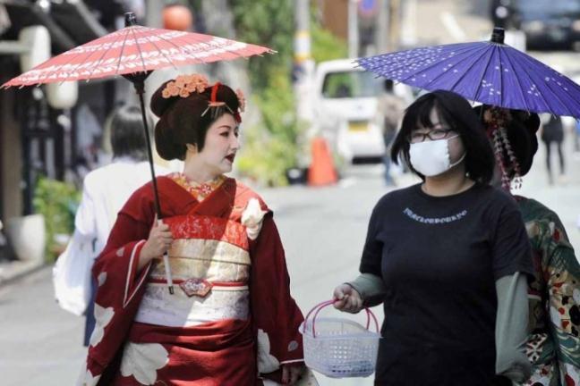 Một geisha đi bộ trên phố cùng người bạn.